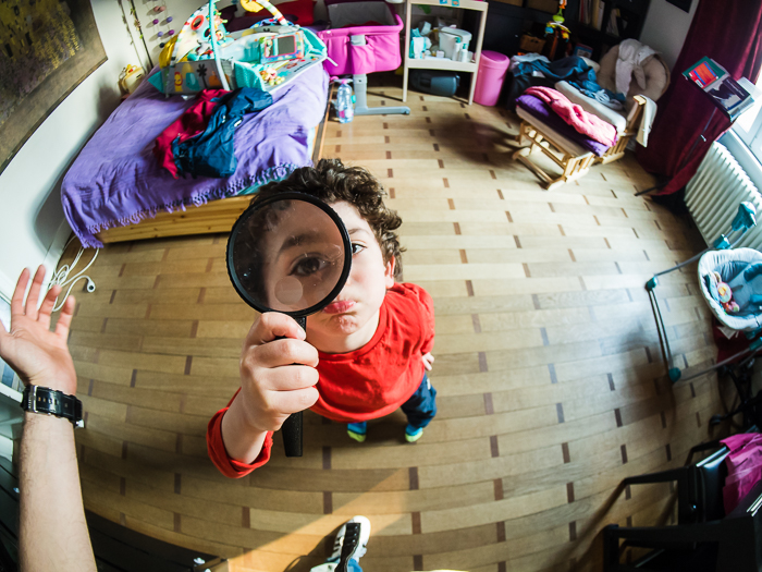 Fisheye lens photo of child holding magnifying glass