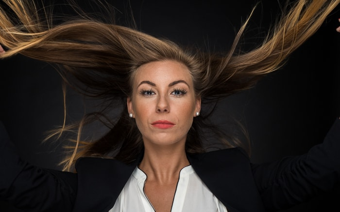 Portrait lighting: medium shot of woman with wind-blown hair