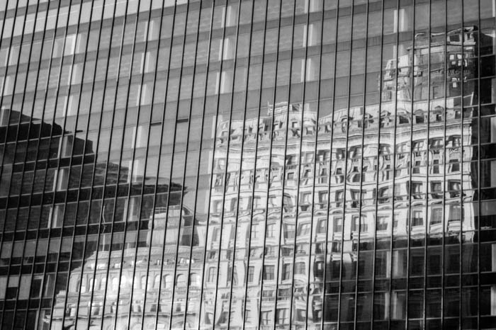 Black and white reflection of a building in the glass windows of another building