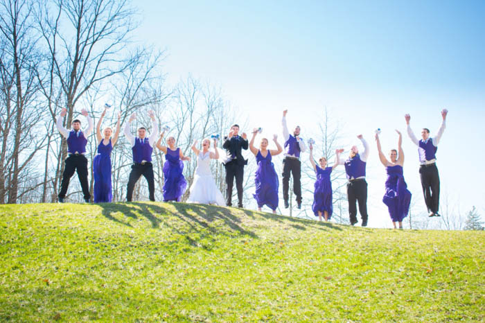 funny creative bridal party pose, jumping up on a hilltop