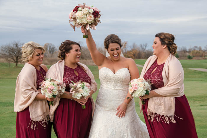 bride and bridesmaids photo, holding the bouquet up in a victory pose