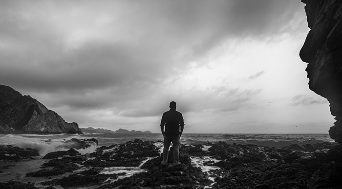 A black and white fine art shot of a man on a beach looking towards the ocean
