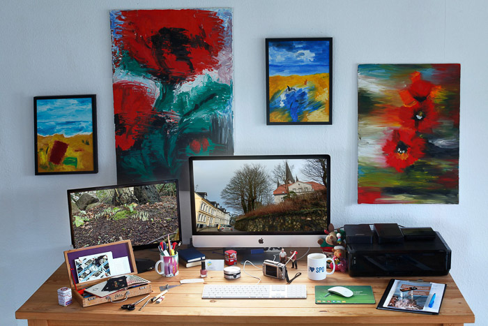 A home office desk surrounded by colorful paintings - color mode in photoshop